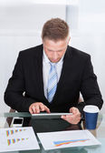 Stylish hardworking businessman using a tablet computer — Stock Photo