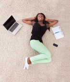 Young African American woman relaxing on rug at home — Stock Photo