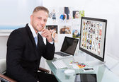 Businessman editing photographs — Stock Photo