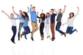 Group of diverse people raising arms and jumping — Stock Photo