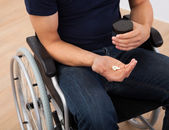 Man Holding Medicine While Sitting On Wheelchair — Stock Photo