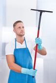 Male janitor using a squeegee to clean a window — Stock Photo