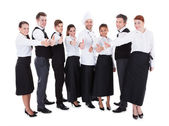Waiters and waitresses showing thumbs up sign — Stock Photo