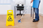 Warning notice as a janitor mops the floor — Stock Photo