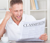Excited man reading the classifieds cheering — Stock Photo