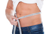 Healthy fit young man measuring his waist — Stock Photo