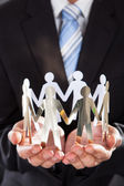 Businessman Holding Metal Team In Cupped Hands — Stock Photo