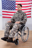 Patriotic Soldier Sitting On Wheel Chair Against American Flag — Stock Photo