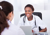 Female dentist talking to patient at desk in clinic — Stock Photo