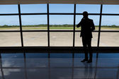 Businessman using mobile phone against airport window — Stockfoto