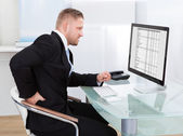 Businessman rubbing his back as he sits working at his desk — Stock Photo