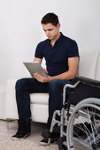 Handicapped Man Using Digital Tablet On Sofa — Stock Photo