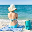 Woman in bikini relaxing on beach towel enjoying the ocean view — Stock Photo #44069119