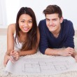 Couple Looking At Blueprint While Sitting On Rug — Stock Photo