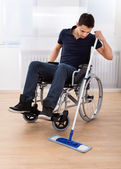 Handicapped Man Mopping Floor While Sitting On Wheelchair — Stockfoto