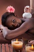 Mujer disfruta de un masaje herbal spa — Foto de Stock