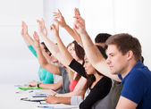 Row Of College Students Raising Hands — Stock Photo