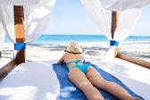 Sexy young woman in gazebo enjoying the ocean view at beach — Foto Stock
