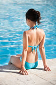 Havuz kenarında oturan genç kadın — Stok fotoğraf