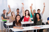 College Students Raising Hands In Classroom — Stock Photo