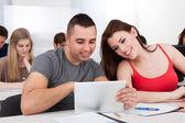 Estudiantes sonrientes usando tableta digital en el aula — Foto de Stock
