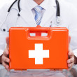Smiling doctor or paramedic with a first aid kit — Stock Photo #44070659