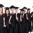 Graduate students standing in row holding diplomas — Stock Photo