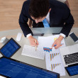 Businessman Examining Graphs At Desk — Stockfoto