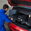 Mechanic Using Laptop While Repairing Car — Stok fotoğraf