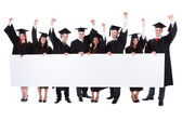Cheerful excited graduate students showing empty banner — Stock Photo