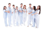 Group of cheerful doctors showing thumbs up — Stock Photo
