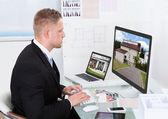 Businessman checking a property portfolio online — 图库照片