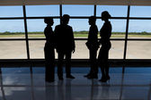 Businesspeople standing against airport window — Stock Photo