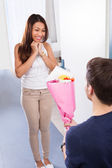 Man Kneeling While Giving Bouquet To Happy Woman — Stock Photo