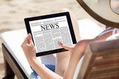 女性のビーチでデジタル タブレットに新聞を読む — ストック写真