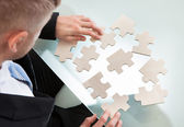 Businessman with a jigsaw puzzle — Foto de Stock