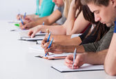 University Students Writing At Desk — Stock Photo