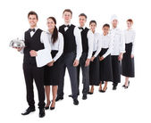 Large group of waiters and waitresses standing in row — Stock Photo