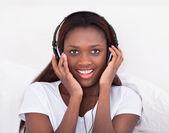 Woman Enjoying Music Through Headphones In Bed — Stock Photo