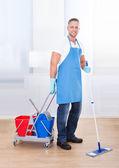 Janitor cleaning wooden floors — Stock Photo
