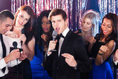 Man Singing Into Microphone With Friends At Karaoke Party — Stock Photo