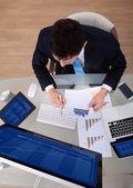 Businessman Examining Graphs At Desk — Stock Photo