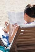Kvinna läser boken på solstol på stranden — Stockfoto