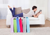 Woman Using Digital Tablet With Shopping Bags On Floor — Stock Photo