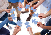 Group of people connecting puzzle pieces — Stock Photo