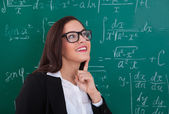 Thoughtful Teacher Looking At Chalkboard — Stock Photo