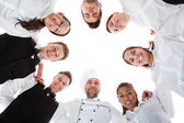 Waiters and waitresses standing in circle — Stock Photo