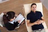Paziente maschio di comunicare mentre psicologo scrivendo note — Foto Stock