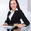 Happy Businesswoman Holding Credit Card At Desk — Stock Photo #44591515