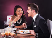 Woman Feeding Man In Restaurant — Stock Photo